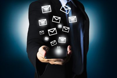 Midsection of man holding a phone with illustrated mail icons coming out of the phone