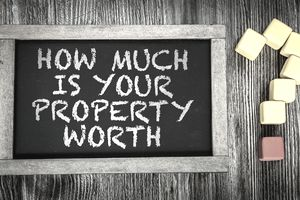 "A sign with the words ""How Much is Your Property Worth? """