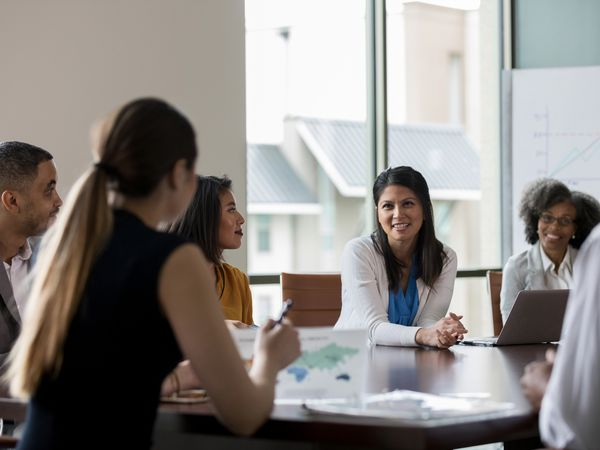 Men and women sit around a conference table in a nonprofit boardroom