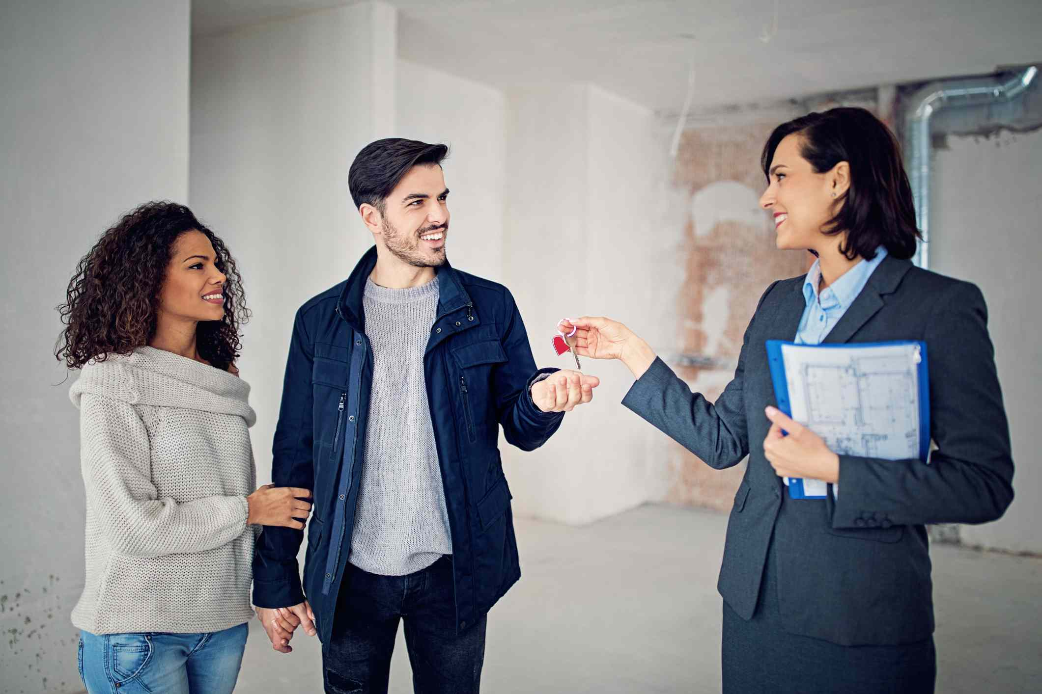 Real estate agent is giving key for a new apartment to happy couple