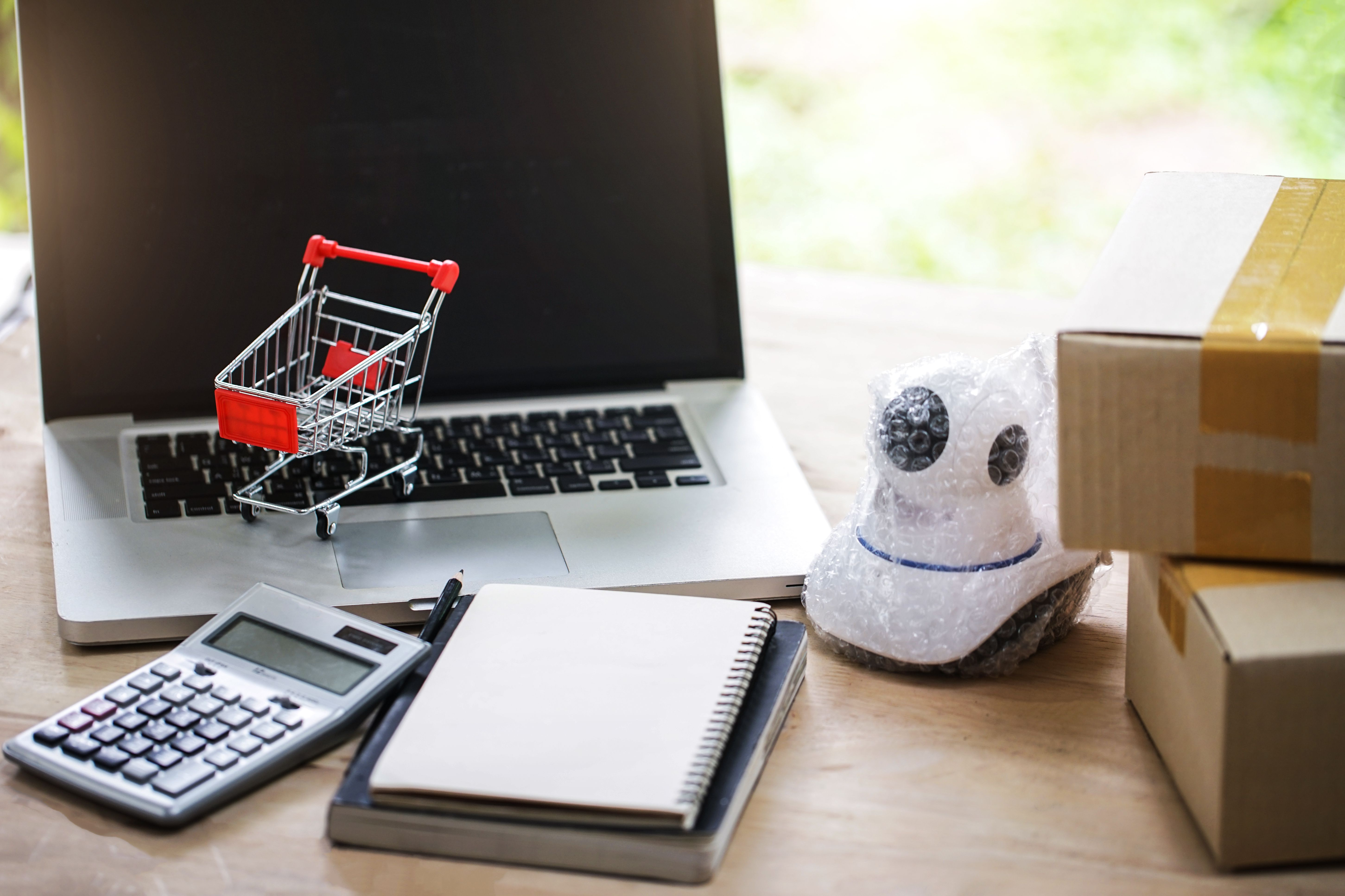 Notebooks, calculator, toy shopping cart and various products and boxes depicting online sales