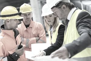 Engineers and construction workers reviewing blueprints at construction site