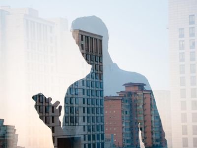 Businessman using smartphone, superimposed over a cityscape of rental properties