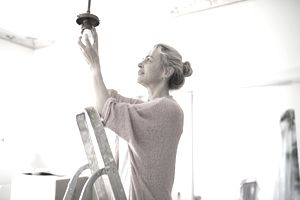 Woman changing light fixture.