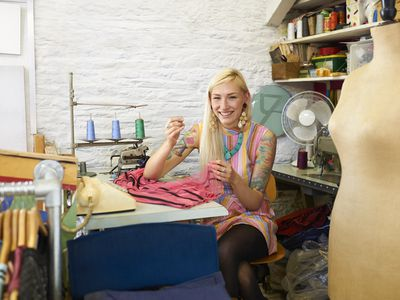 Woman repairing dress in vintage clothes shop.