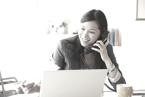 real estate agent on the phone at a desk in front of a laptop
