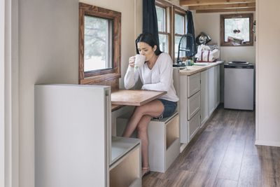 Young woman having tea in her tiny house