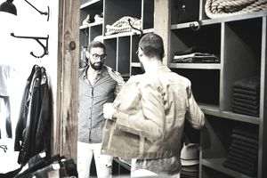 Man trying on jacket while looking in the mirror in mens clothing shop