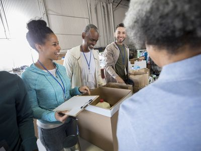 A mid adult woman laughs with a group of fellow food bank volunteers. She holds a clipboard ready as she organizes the packing of boxes.