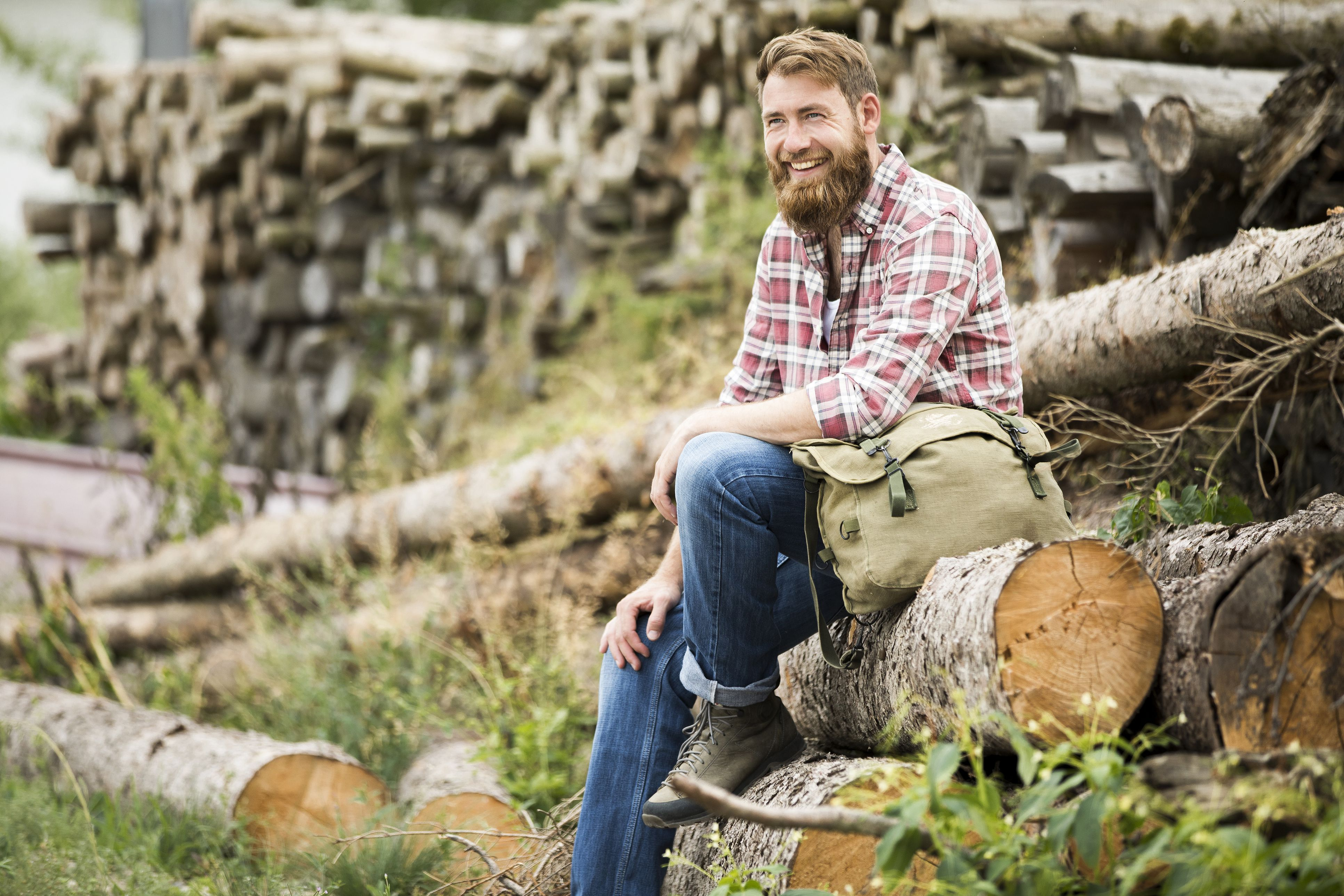 Laughing bearded man sitting on stack of fresh-cut timber