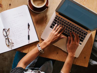 Freelance writer typing on laptop from coffee shop