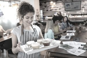 Waitress holding a tray with latte and coffee for customers.at background