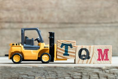 Toy forklift carrying blocks that spell TQM for total quality management.