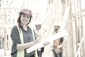 A low income housing builder make notes on her blueprints.