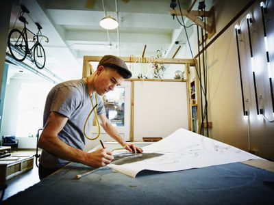 Independent Contractor working on mechanical drawing in their shop.