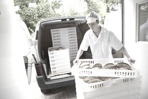 Delivery driver loading bread into back of delivery truck/