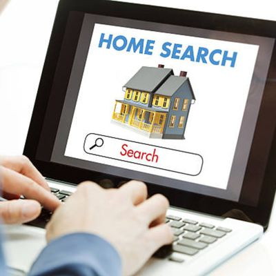 Male using a laptop to search homes on a real estate website