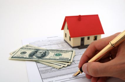 house and money sitting on paperwork being signed