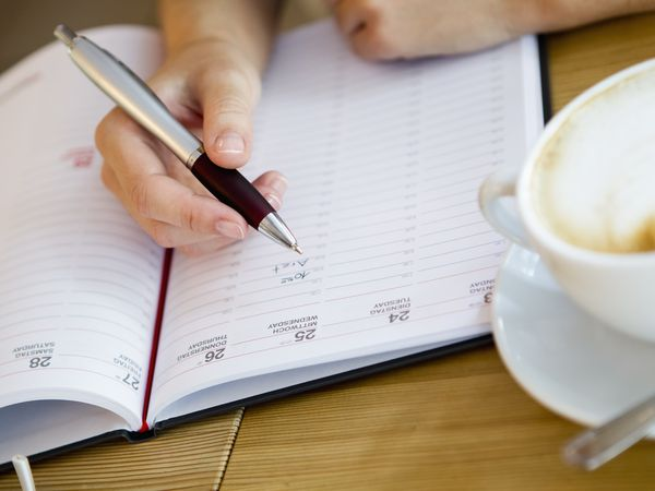 Close up of woman writing in planner