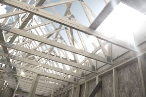 Sun shining through wood framed roof trusses on house under construction.