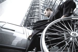 Wheelchair-using business executive turning key in car door