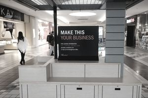 "Empty retail kiosk in a mall with a sign that says, ""Make this your business."""