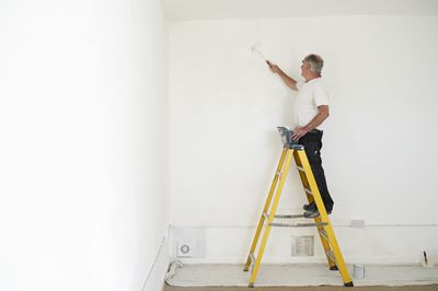 An man on a step ladder repainting walls after removing lead based paint.
