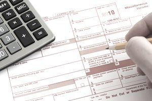 Person filling out IRS 1099 tax form with pencil and calculator
