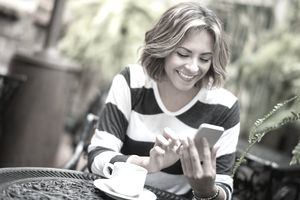 Young woman texting a charitable donation on her mobile phone.