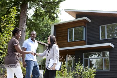 A real estate agent greeting a couple at a house viewing