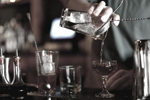 Closeup of bartender's hand pouring cocktails