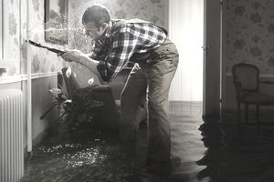 Plumber fixing a pipe in a flooded room
