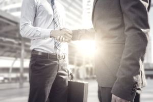 Businessman handshake at city outside office.