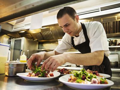 Chef standing in kitchen, wearing apron, adding salad garnish to plates of food.
