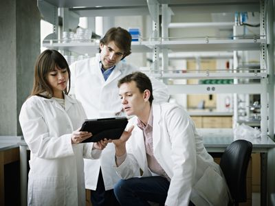 Scientists discussing work on digital tablet