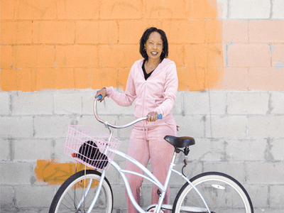 woman standing with a bike by a painted wall of concrete blocks