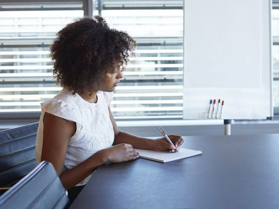 Woman writing a letter in office