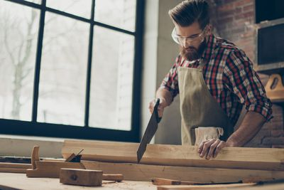 young stylish cabinet-maker with glasses and hairstyle. Strong handsome craftsman holding saw and wood blank at workplace