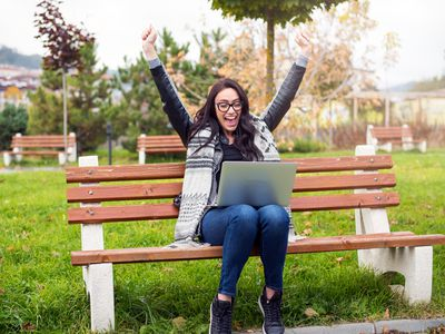 Happy young woman, sitting on park bench with laptop in her lap, hands raised and mouth open in excited smile celebrating