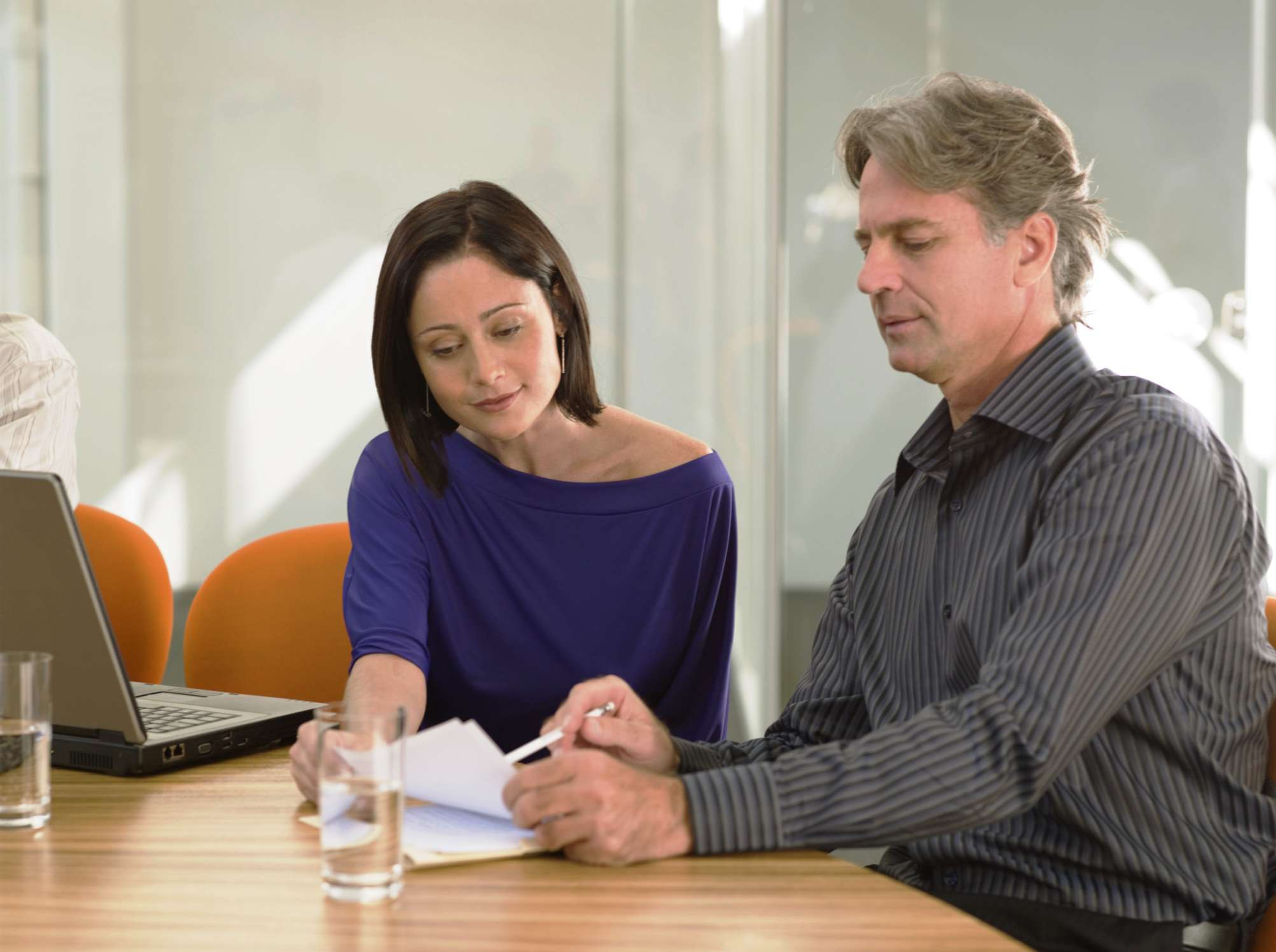 Woman delegating tasks to a man from a notebook