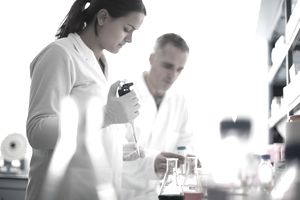 Two people wearing lab coats working in a laboratory