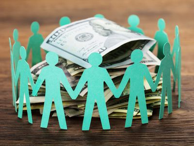 cut-out figures encircle stack of 100 dollar bills