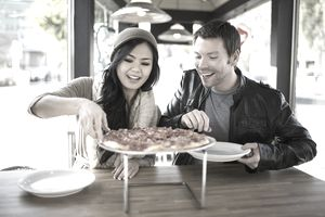 a young couple eating pizza.