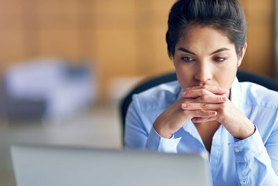 Woman looking thoughtful as she researches the pros and cons of self-employment
