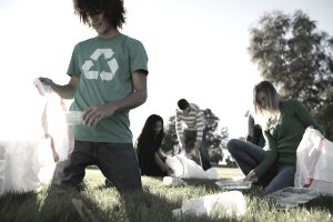 Several people in a park setting picking up trash to recycle.