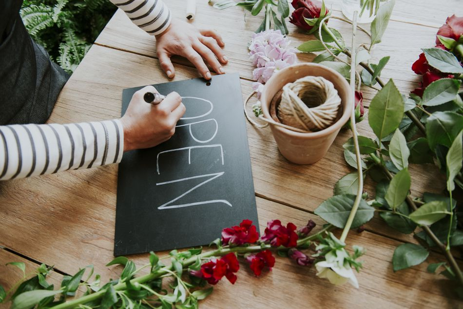 Florist in flower shop, writing Open sign, mid section