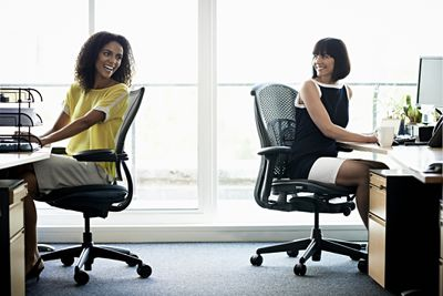 Two women laughing sitting in office chairs