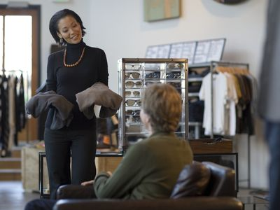 image consultant showing clothing pieces to a client.