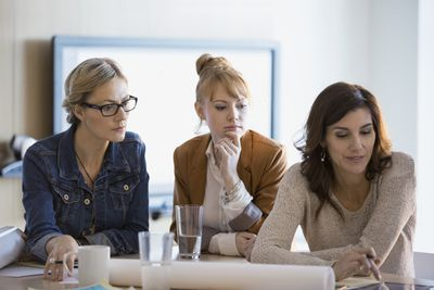 Business women looking at plans in a meeting