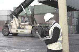 Heavy equipment listing a container at a dock while another worker in a hardhat checks the load using Manugistic Software.